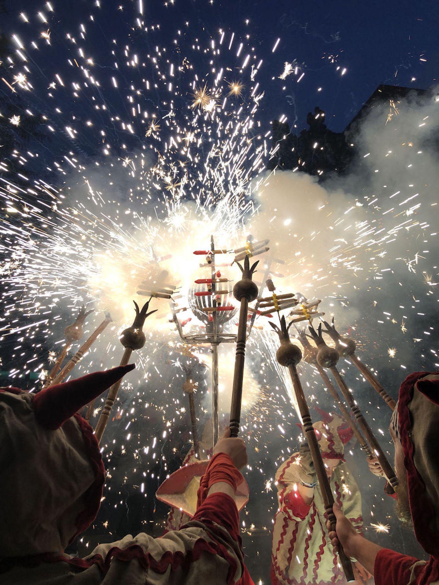 Correfocs durante um tradicional festival catalão, onde grupos vestidos de demônios acendem fogos de artifício na multidão