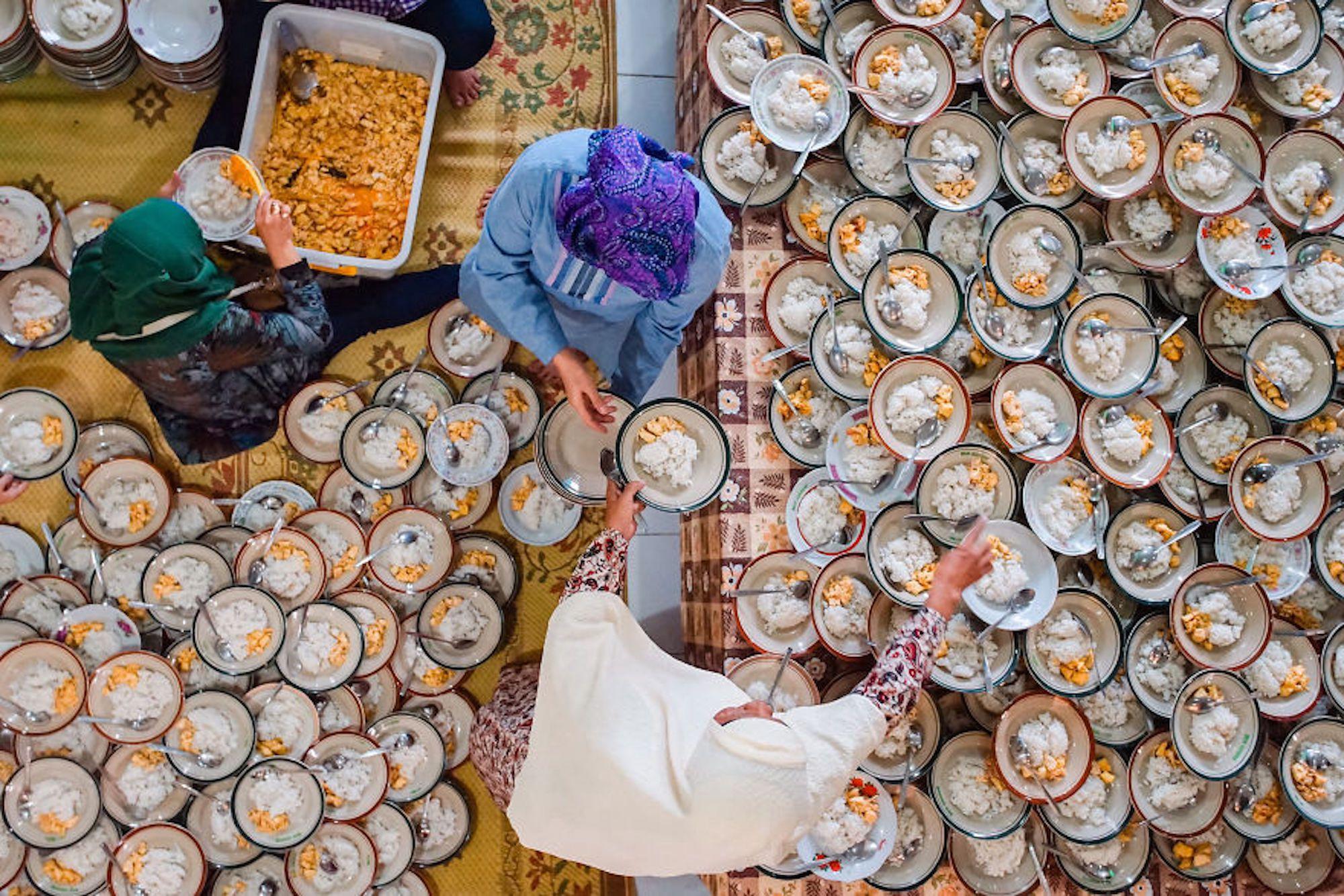 Três voluntários servem 1.000 pratos de frango e arroz preparados para o Iftar, uma refeição noturna servida no Ramadã